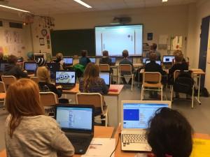 bilde som viser barn sitte foran sine datamaskiner, med en instruktør som viser hva de skal gjøre.
